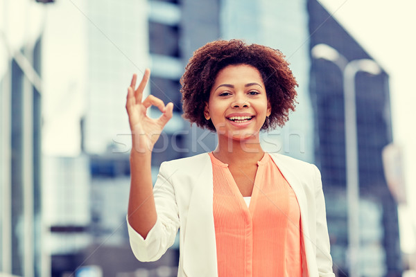 happy african businesswoman showing ok in city Stock photo © dolgachov