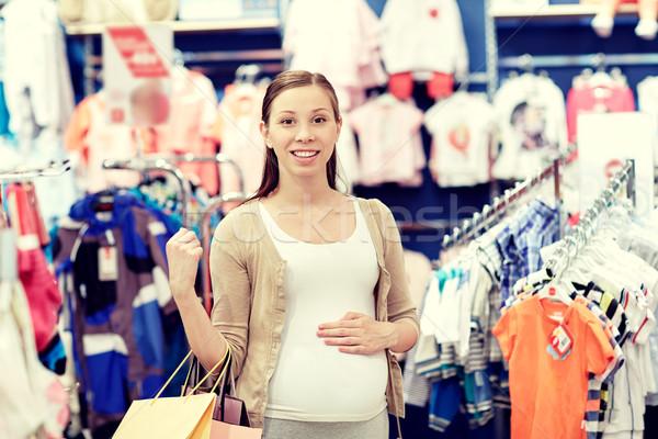 Feliz mulher grávida compras roupa armazenar gravidez Foto stock © dolgachov