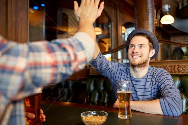 happy male friends making high five at bar or pub Stock photo © dolgachov