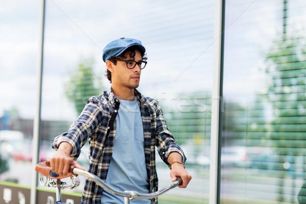 hipster man walking with fixed gear bike Stock photo © dolgachov