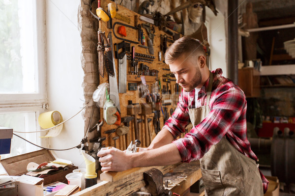 carpenter working with plane and wood at workshop Stock photo © dolgachov