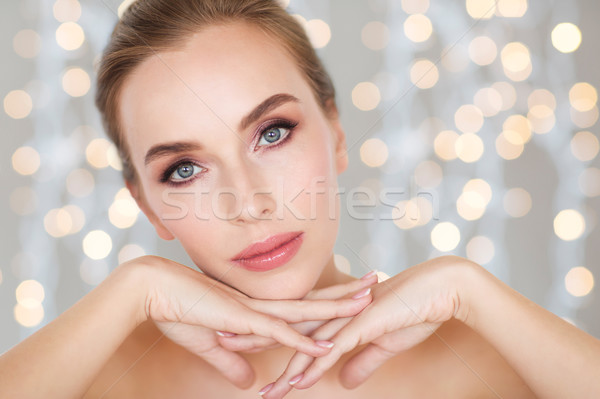 beautiful young woman face and hands over lights Stock photo © dolgachov