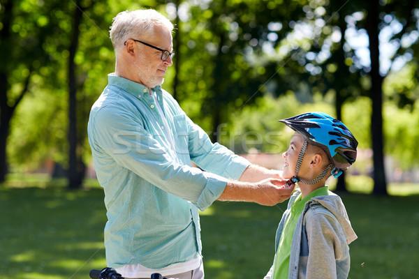 old man helping boy with bike helmet at park Stock photo © dolgachov