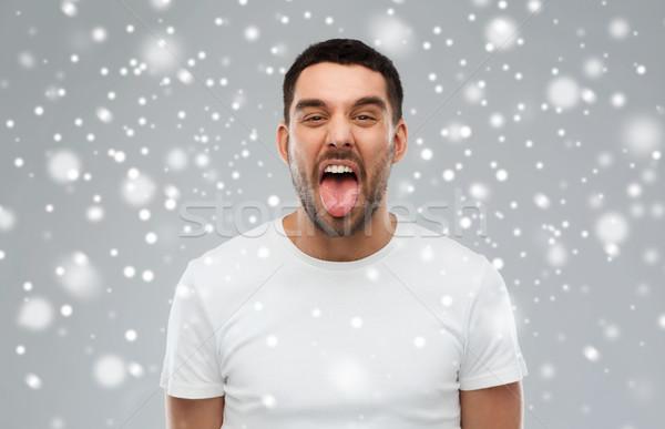 Férfi mutat nyelv hó gorombaság tél Stock fotó © dolgachov