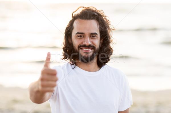 happy smiling man with beard on beach Stock photo © dolgachov
