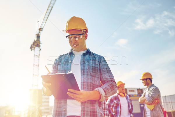 Stock photo: builder in hardhat with clipboard at construction