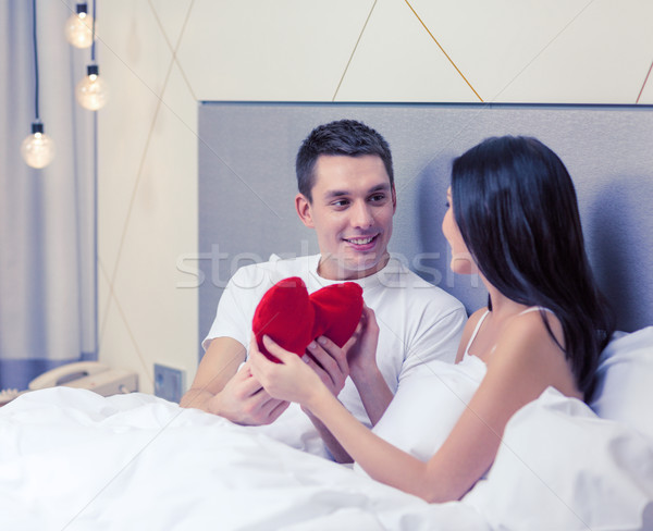 smiling couple in bed with red heart shape pillow Stock photo © dolgachov