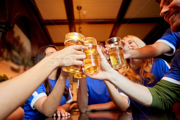 football fans clinking beer glasses at sport bar Stock photo © dolgachov