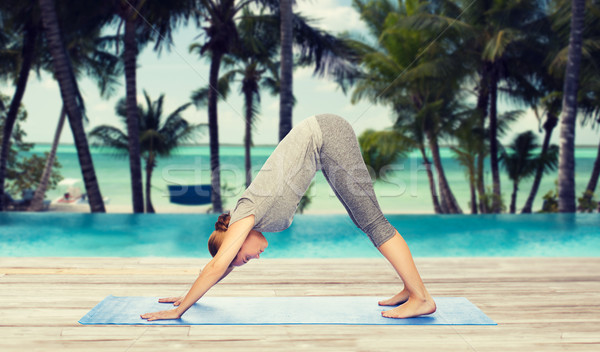 woman making yoga dog pose on mat Stock photo © dolgachov