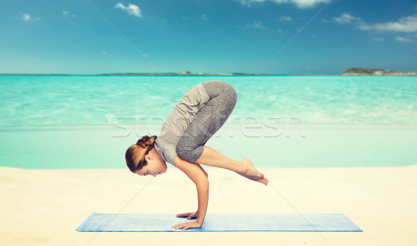 woman making yoga in crane pose on mat over beach  Stock photo © dolgachov