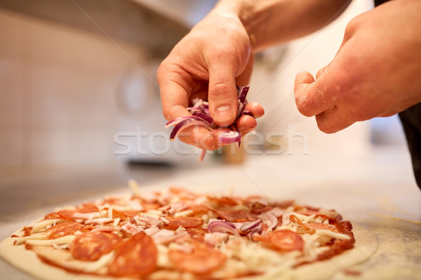 cook adding onion to salami pizza at pizzeria Stock photo © dolgachov