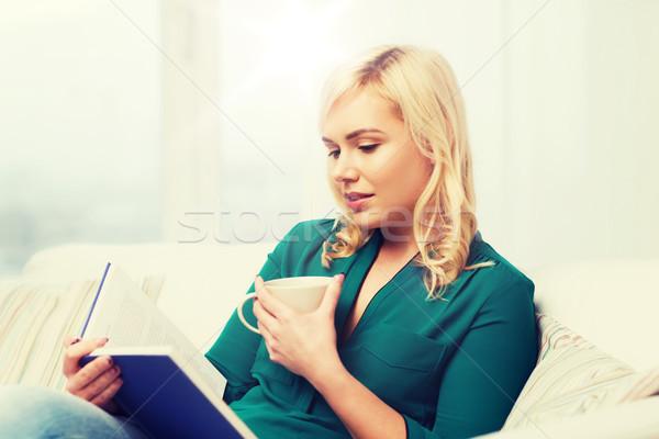 Fiatal nő teáscsésze olvas könyv otthon szabadidő Stock fotó © dolgachov