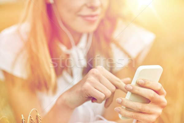 Közelkép nő okostelefon fülhallgató nyár ünnepek Stock fotó © dolgachov