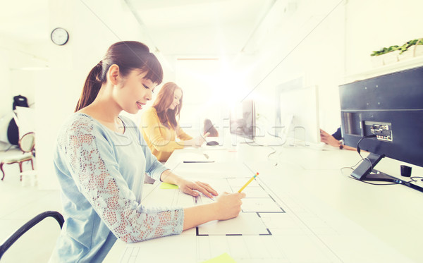 Stock photo: architect woman drawing on blueprint at office