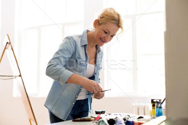 happy woman artist painting at art studio Stock photo © dolgachov