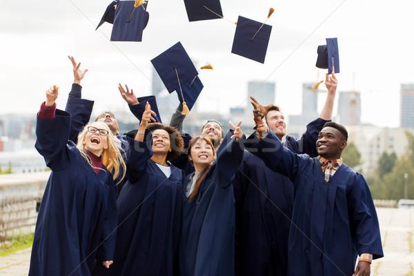 happy graduates or students throwing mortar boards Stock photo © dolgachov