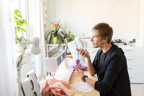 fashion designer with smartphone working at studio Stock photo © dolgachov