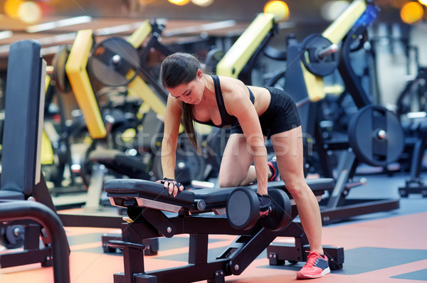 young woman flexing muscles with dumbbell in gym Stock photo © dolgachov