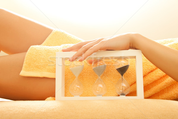 hands and legs in spa salon with a sandglass Stock photo © dolgachov