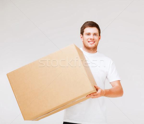 smiling man carrying carton box Stock photo © dolgachov