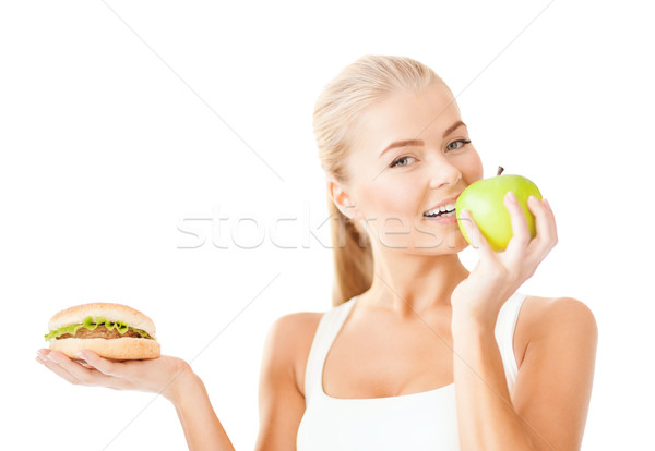smiling woman with apple and hamburger Stock photo © dolgachov