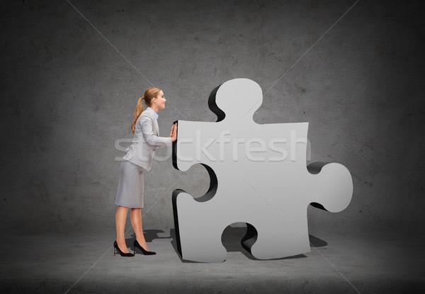 Stock photo: smiling businesswoman pushing big puzzle piece