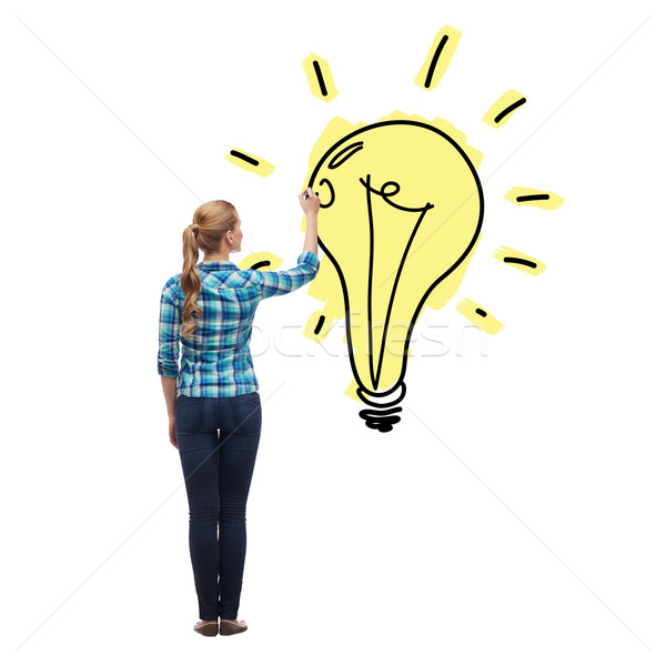 woman from the back drawing light bulb in the air Stock photo © dolgachov