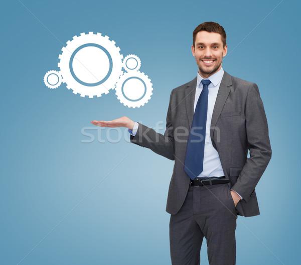 smiling businessman holding settings icon Stock photo © dolgachov