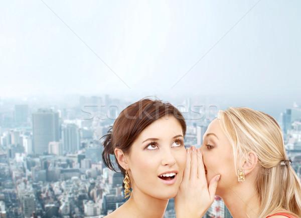 two smiling women whispering gossip Stock photo © dolgachov