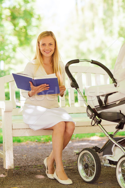 happy mother with book and stroller in park Stock photo © dolgachov