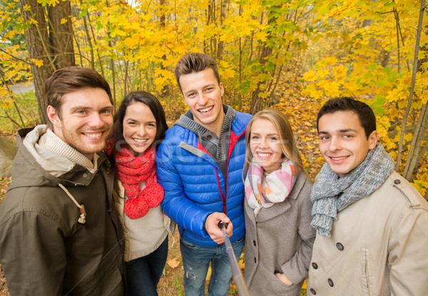 smiling friends taking selfie in autumn park Stock photo © dolgachov