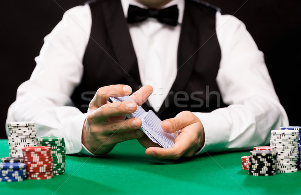 holdem dealer with playing cards and casino chips Stock photo © dolgachov