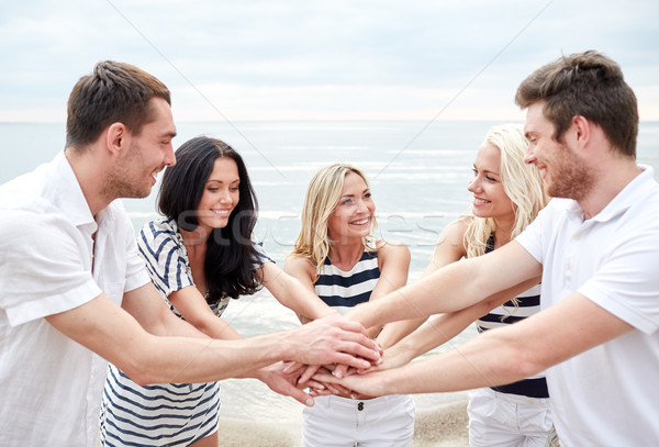 smiling friends putting hands on top of each other Stock photo © dolgachov