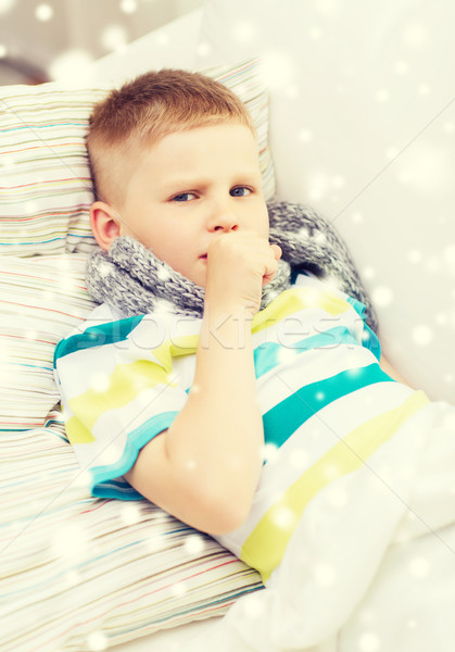 ill boy with scarf lying in bed and coughing Stock photo © dolgachov