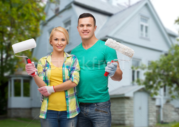 smiling couple with paint rollers over house Stock photo © dolgachov