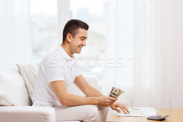 man with papers and calculator at home Stock photo © dolgachov