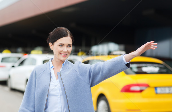 smiling young woman waving hand and catching taxi Stock photo © dolgachov