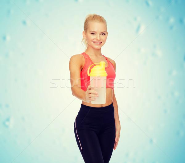 Sorridente mulher proteína tremer garrafa Foto stock © dolgachov