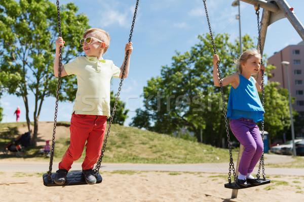 two happy kids swinging on swing at playground Stock photo © dolgachov