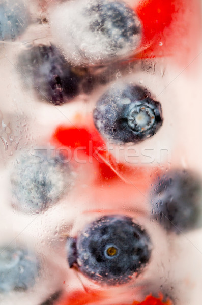close up of fruit water with ice cubes over glass Stock photo © dolgachov