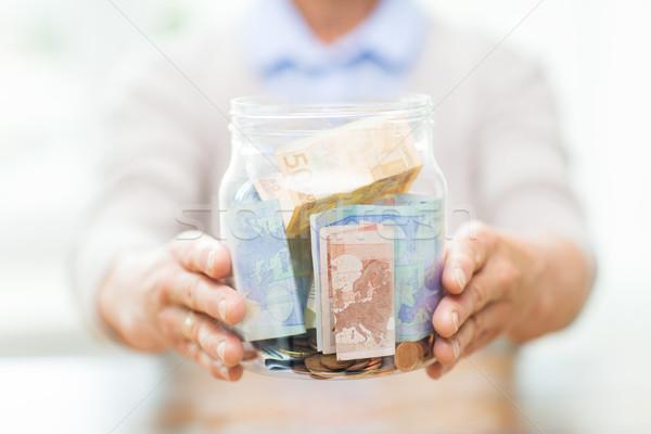 Kıdemli kadın para cam kavanoz Stok fotoğraf © dolgachov