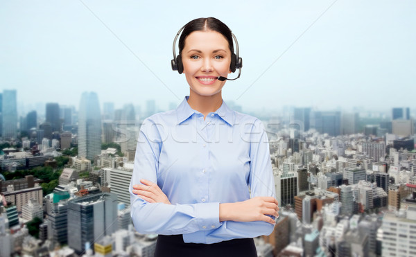 helpline operator in headset over city background Stock photo © dolgachov