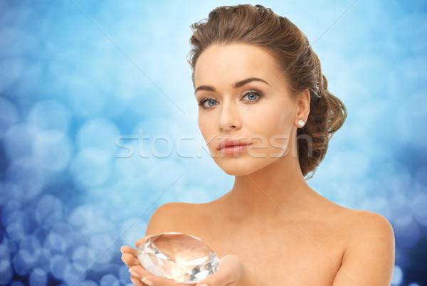 woman showing big diamond over blue lights Stock photo © dolgachov