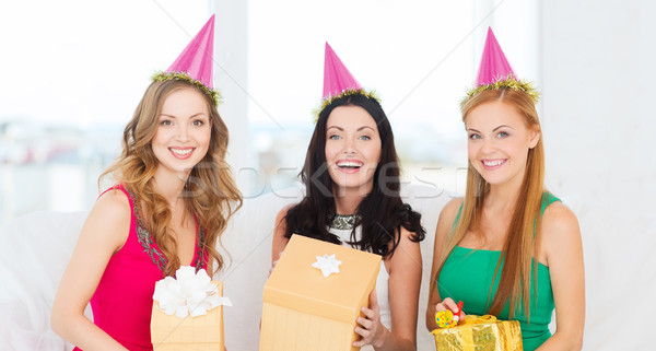 three smiling women in pink hats with gift boxes Stock photo © dolgachov