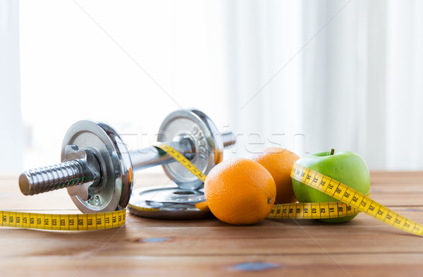 close up of dumbbell, fruits and measuring tape Stock photo © dolgachov