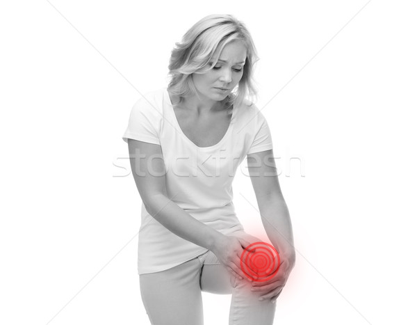unhappy woman suffering from pain in leg Stock photo © dolgachov