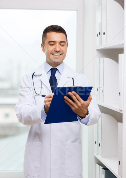 happy doctor with clipboard in medical office Stock photo © dolgachov
