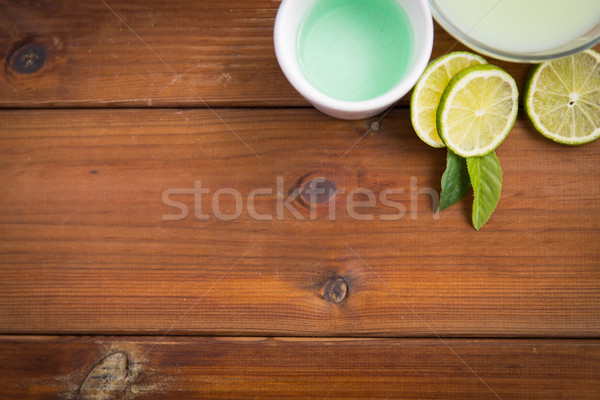close up of body lotion, cream and limes on wood Stock photo © dolgachov
