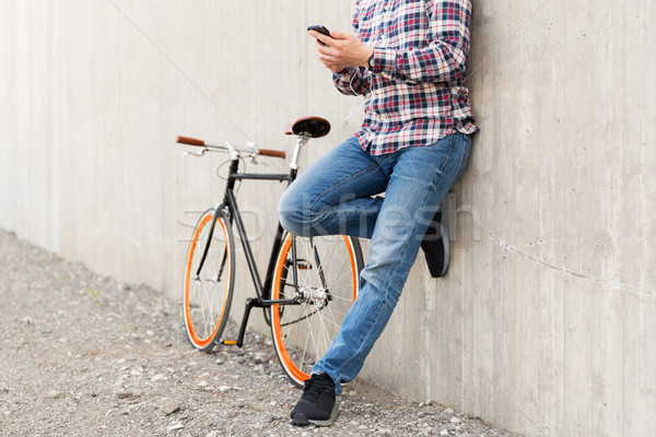 close up of hipster man with smartphone and bike Stock photo © dolgachov