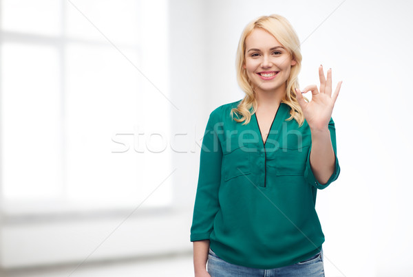 smiling young woman in shirt showing ok hand sign Stock photo © dolgachov